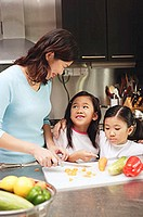 Mother cutting vegetables in kitchen, daughters standing next to her