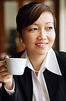 Businesswoman holding cup, looking away