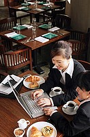 Businesswomen at cafe, using laptop