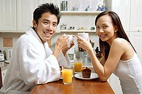 Couple in kitchen, having breakfast, smiling at camera