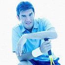 Portrait of a young man resting his hand on a tennis racket