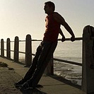 Side profile of a man stretching on the railing of a pier