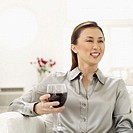 Young woman sitting holding a glass of red wine