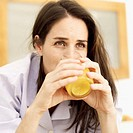 Close-up of a young woman drinking orange juice