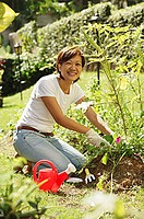 Woman gardening, smiling at camera