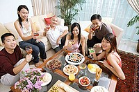 Adults sitting in living room, having a party, smiling at camera