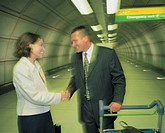 two business executives shaking hands at the airport (toned, blurred)