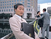 businesswoman standing against a railing and holding a briefcase