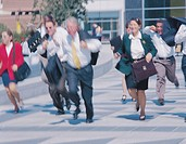 business executives running on a city sidewalk