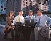 business people talking while sitting outdoors near office buildings