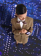 high angle view of a business woman standing on a circuit board making notes