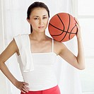 Portrait of a young woman standing holding a basketball over her shoulder