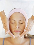 close-up of a young woman getting a face massage from a massage therapist