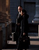 Side profile of a young businessman and a young businesswoman standing outdoors holding briefcases