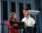 Young businesswoman standing outdoors holding a laptop with a businessman talking to her