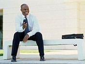 businessman sitting on a bench holding a mobile phone