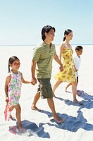 parents and their children walking on the beach