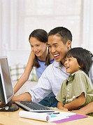 father and his children sitting in front of a computer