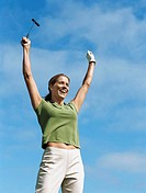 Low angle view of a young woman holding a golf club