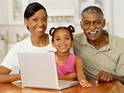 portrait of grandparents and their granddaughter in front of a laptop