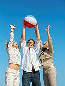 low angle view of two young women reaching out for a beach ball held by a young man