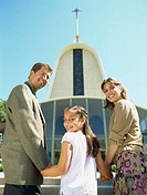 portrait of parents and their daughter standing in front of a church