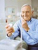 senior man talking on the phone holding a pill bottle