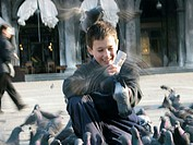 Close-up of a boy feeding pigeons