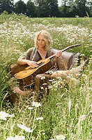Mid adult woman playing a guitar in a garden