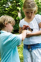 Close-up of a girl and her brother petting a hamster