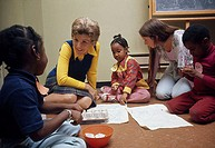 Child psychologist sitting with children, 1970s