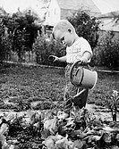 Side profile of a boy watering plants