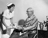 Side profile of a female nurse serving food to a senior man sitting in a wheelchair