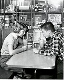 Side profile of a young couple drinking a milkshake in a restaurant, 1954