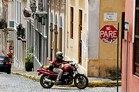 Calle del Sol, architecture, steep hill, motorcycle, adoquine cobblestone, stop sign. Old San Juan. Puerto Rico.