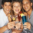 Two young men and one young woman drinking cocktails