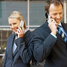 Businessman and businesswoman both using mobile phones