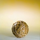 A ball of elastic bands on a yellow background