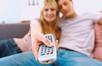 Close-up of a young couple sitting on a couch with a remote control (blurred)