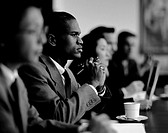 black and white side profile of a man sitting with co-workers at a meeting
