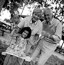 black and white portrait of grandparents at the swings with their granddaughter