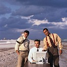 view of three businessmen working on a computer at the beach