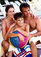 young couple sitting with their son holding a beach ball