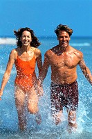 a young couple holding hands and running in the water