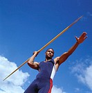low angle view of a young male athlete with a javelin