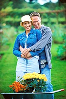portrait of a couple hugging behind a wheel barrow full of flowers