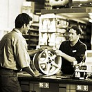 black and white portrait of a young sales man handing a hub wheel of a car to a female customer