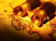 sepia toned close-up of binoculars lying on a map