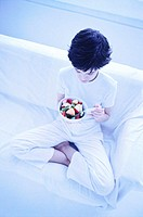 tungsten high angle view of a young woman eating a bowl of fruit