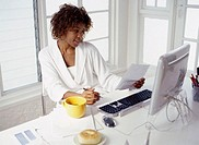 young woman sitting at a desk in front of a computer reading a sheet of paper
